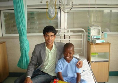Ahmed Paruk presenting a sick child with a new laptop computer