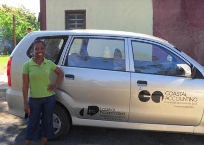 Phumla posing next to the company vehicle