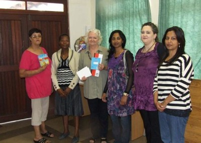 Nokthula, Fehmida, June & Charmaine handing over building vouchers, fans and stationery to Olive Smith, Principal of Merlewood Crechè